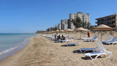Stranden framför övergivna Varosha med de tomma strandhotellen i bakgrunden.