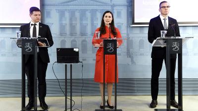 Mikko Koskinen, Sanna Marin och Ahti Kurvinen står på en rad framför talarpodium.