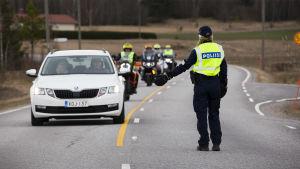 Poliisi pysäyttää auton ja moottoripyöriä Pukkilan karanteeni rajalla.