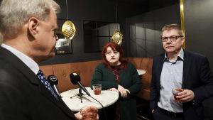 Tre personer står och sitter vid runt bord. På bordet står glas och mikrofoner.