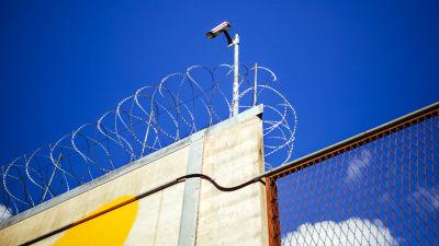 Kamera och taggtråd vid fängelse.