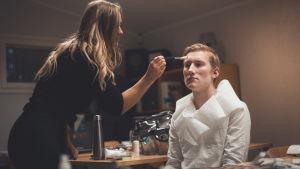 En kvinna sminkar en man inför en filminspelning.