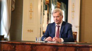 President Sauli Niinistö sitter vid ett skrivbord av trä.Han har kostym och slips på sig.