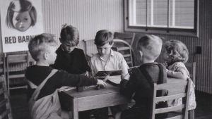 Mustavalkea kuva, jossa lapset kokoontuneet luokkahuoneessa pöydän äärelle