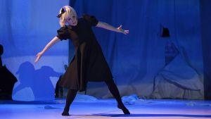 Mari Rosendahl tanssimassa yllään väljä polvipituinen mekko ja rusetti hiuksissaan.