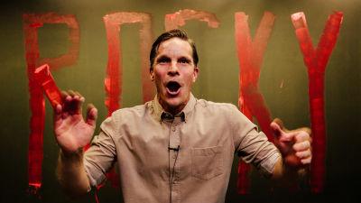 På bilden syns en energisk skådespelare Martin Bahne med armarna i luften och öppen mun. Han är iklädd en beige skjorta och i bakgrunden står det ROCKY skrivet med röda bokstäver.