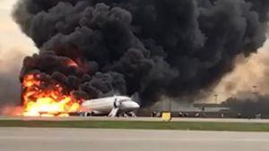 Ett flygplan brinner på landningsbanan i Moskva, svart rök stiger upp.