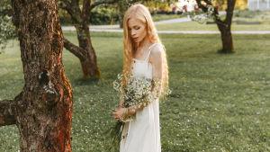 Amanda Parkkinen med blommor i handen vid ett träd