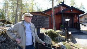 Pentti Kronqvist står framför en gammal träkyrka.