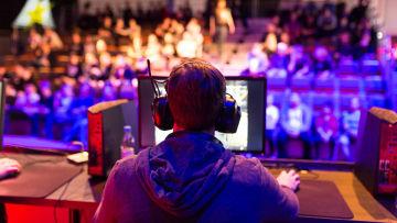 En ung man sitter med hörlurar och mikrofon på sig framför en dator på ett stort e-sportevenemang.