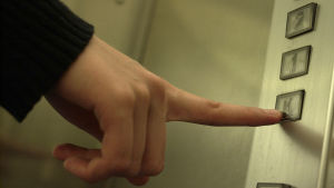 Finger trycker på en hissknapp.