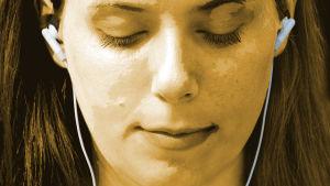 Flicka lyssnar på musik via hörlurar.