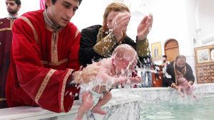 Flera män som är klädda i prästkåpor. Två spädbarn doppas i en stor bassäng under ett dop i Georgien.