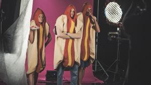 """Simon Karlsson, Johanna Dikert och Oliver Kivi poserar i studio. Bakom kulisserna-bild för musikvideon """"Jag vill har korv""""."""