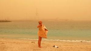 Kvinna vid stranden i sandstorm på Kanarieöarna