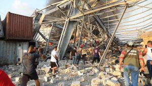 Personer som rör sig bland stenar och rasmassor efter explosion i Beirut.