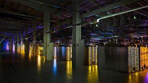 En mörklagd lokal lyses upp i olika färger av komponenterna i datacentret i Fredrikshamn.