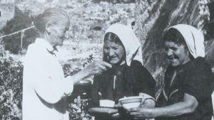Hilma Granqvists sageskvinnor Sitt Louisa, Alya Ibrahim och Hamdiya Sanad i byn Artas i Palestina. Här delar Sitt Louisa ut socker till Alya och Hamdiya. I förgrunden syns Hilmas egen skugga, som den ofta gjorde på hennes fotografier.