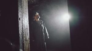 En väldigt grå och mörk bild (förutom ett starkt ljussken) på en man i hjälm som är inne i ett mörkt ställe. Det är en bunker.