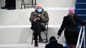 Bild på Bernie Sanders som sitter på stol iklädd munskydd och vantar.