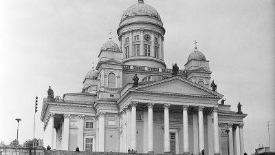 Helsingin Suurkirkko 1960-luvulla. Autoja pysäköityinä kirkon portaiden edustalle. Mies kävelee Senaatintorin poikki.