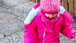 Ett barn i knallrosa vinterkläder och gummistövlar står i en vattenpöl