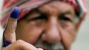 En irakisk man i Bagdad visar upp sitt bläckmärkta finger, beviset på att han röstat i lördagens val.