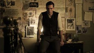 Tolkien står lutad mot sitt skrivbord.
