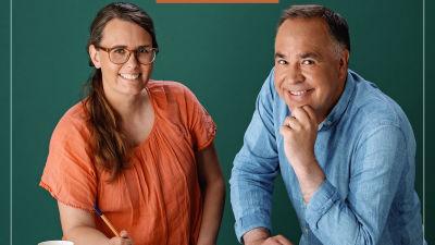 Jenny och Jens sitter vid ett vitt bord och småler rakt in i kameran. På bordet ligger tidningar med korsord uppslagna.