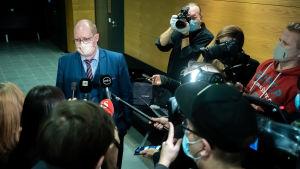 Advokat Jussi Sarvikivi står i en korridor omringad av journalister.