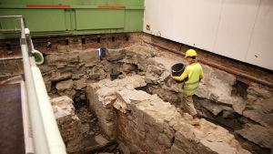 En person går med ett ämbare på arkeologiska utgrävningarna i Katedralskolan i Åbo.