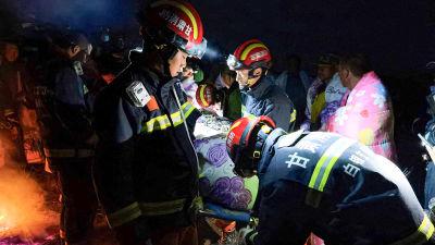 Räddningsarbetare bär en person på bår efter att extremväder slagit till under ett ultramaraton i provinsen Gansu i Kina.
