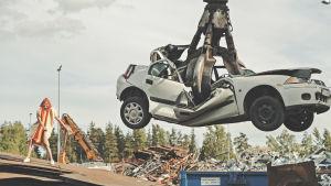 """Skrotig bil lyft upp med en kran på """"bilskrotningsplats"""". Nådon dansar i korvdräkt i bakgrunden. Insp. för musikvideo av """"Jag vill ha korv""""."""
