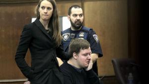 Nainen, mies ja poliisi oikeussalissa. Nainen pitää kättänsä silmiään pyyhkivän, tuolilla istuvan miehen olalla.