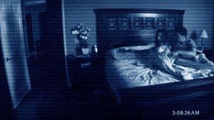 En man och en kvinna sitter i sängen mitt på natten och ser mot en öppen dörr.