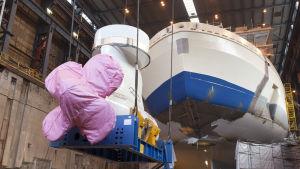 Ett kryssningsfartyg som håller på byggas. Fartygets propeller ska fästas.