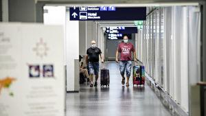 Två resenärer går med varsin kappsäck på Helsingfors-Vanda flygfält. Båda bär ansiktsskydd.