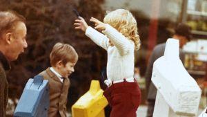 Katja Lindroos lapsena Tapiolan Heikintorin puuhevosen päällä