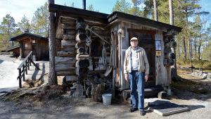 Pentti Kronqvist står framför en gammal jaktstuga av trä.