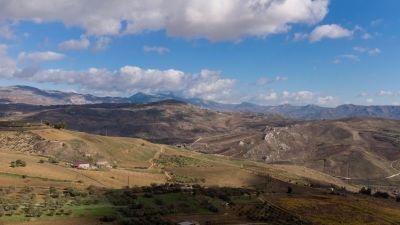 Vy över ett stort område med odlade fält och träddungar som omger några hus på Sicilien.