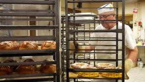 Leipuri Pekka Pihlaja paistaa pullia leipomossa.