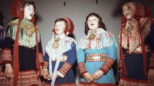 Saamelaisia lapsia laulamassa saamelaisten kansanpuku yllään