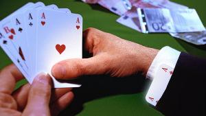 En hand håller i spelkort, på bordet ligger sedlar.