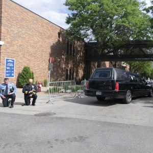 Kaksi polvistunutta poliisia, ruumisauto ja joukko kuvaajia.