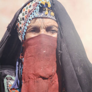 Iäkäs beduiininainen otsan ja kasvojen alaosan peittävässä perinteisessä asussa.