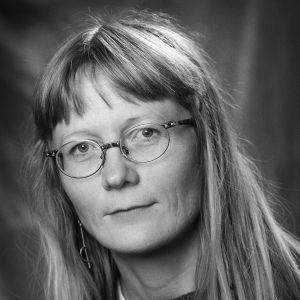 En svartvit bild av en kvinna i medelåldern med långt, blont hår. Hon har glasögon på sig och tittar rakt in i kameran.