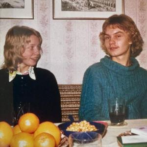Nuori nainen ja mies istuvat pöydän ääressä 70-luvun valokuvassa.