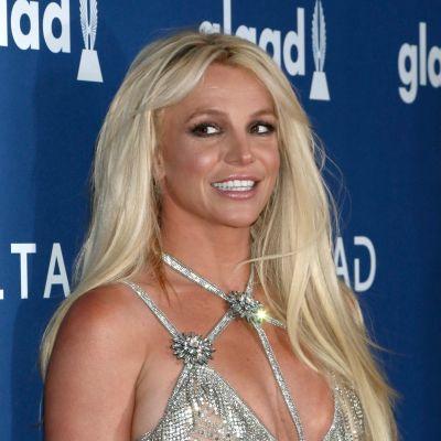 Britney Spears ler och tittar åt sidan medan hon poserar på röda mattan.