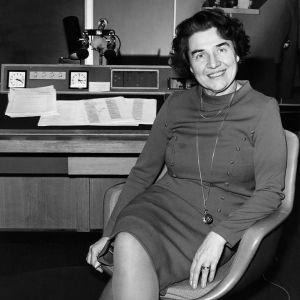 Radiokuuluttaja Kaisu Puuska-Joki istuu studion tuolilla ja hymyilee kameralle vuonna 1960.