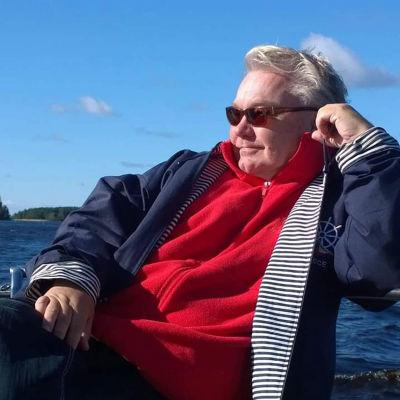 Keski-ikäinen mies istuu nojaillen kädellään kaiteeseen. Taustalla näkyy poutataivas ja meri.